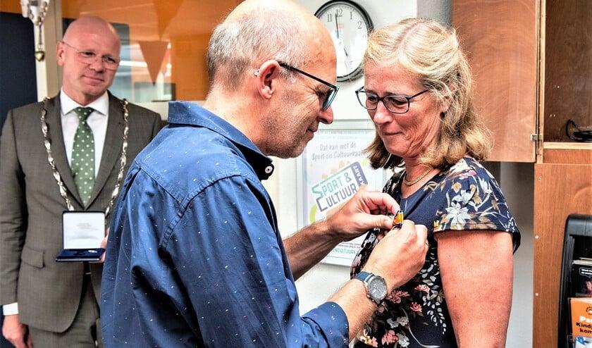 <p>De onderscheiding wordt Renie Luteijn opgespeld door haar echtgenoot terwijl de burgemeester toekijkt (foto: Michel Groen).</p>