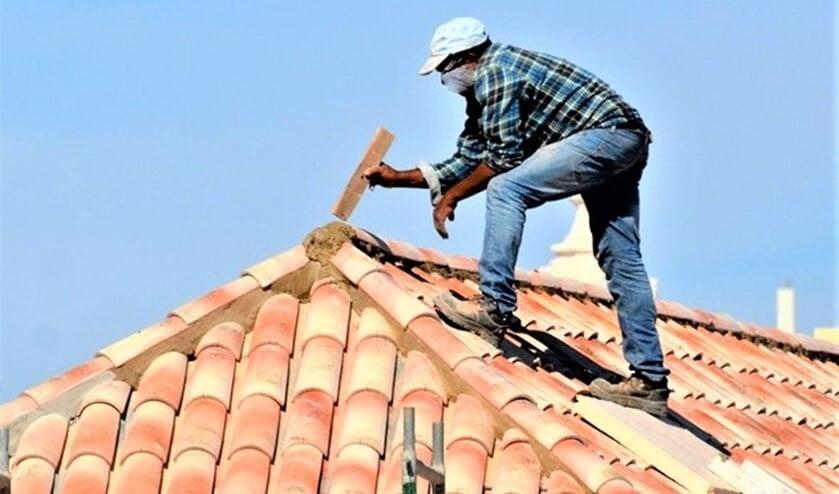 <p>Oplichters bieden bijvoorbeeld werkzaamheden aan het dak aan (stockfoto van onbekend persoon die werk op een dak verricht).&nbsp;</p>