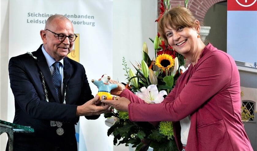 <p>Noor Kamerbeek ontvangt de gemeentelijke onderscheiding de UBU uit handen van burgemeester Jules Bijl (foto: Hilbert Krane).</p>