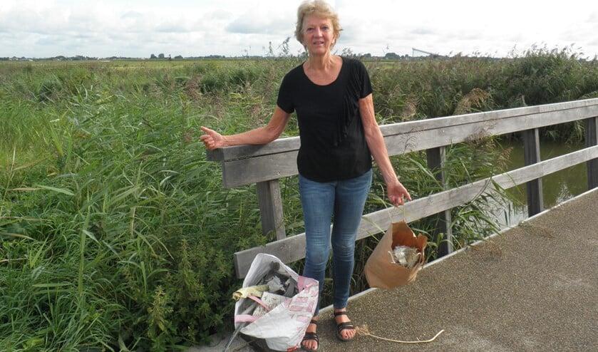 Joke Verplanke bij de ingang aan de Houtkade van de Nieuwe Driemanspolder (Leidschenveen) toont het sloopafval, dat zij eerder dit jaar opraapte. Foto Kees van Rongen