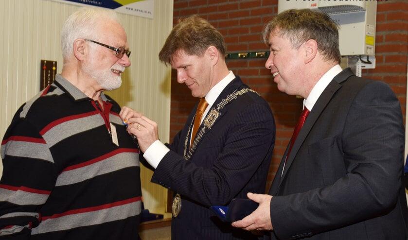 Locoburgemeester Jan Loonen speldt de onderscheiding op. Rechts gedeputeerde Patrick van der Broeck.  Foto: Hoedemaekers Venray.