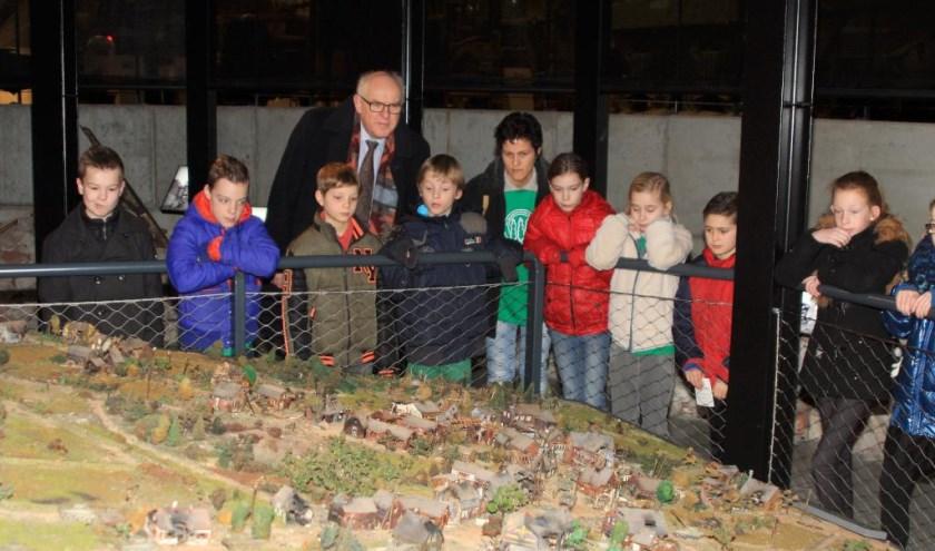 Burgemeester Van Soest van de gemeente Boxmeer met een groep leerlingen van een basisschool uit Boxmeer, bij een maquette van het in 1944 verwoeste Overloon.
