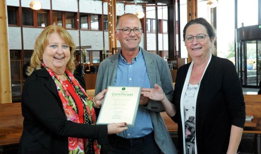 Directeur Stichting Accessibility, Yolande Mansveld, overhandigt het certificaat aan de voorzitter van de Cliëntenraad van VieCuri, Jack Arts, en lid van de Cliëntenraad Marie-Christine Hulsbeck.