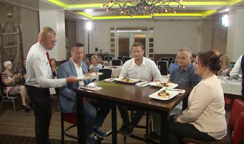 Presentator Rob van Lieshout samen  met de drie gasten aan tafel.
