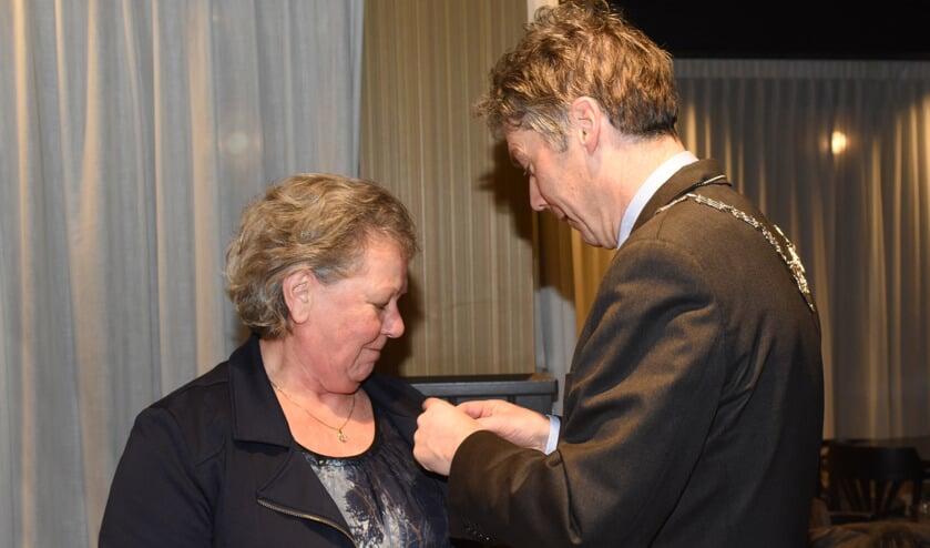 Burgemeester Hans Gilissen spelt de onderscheiding op bij Ria Flinsenberg-Steeghs. Foto: Hoedemaekers.