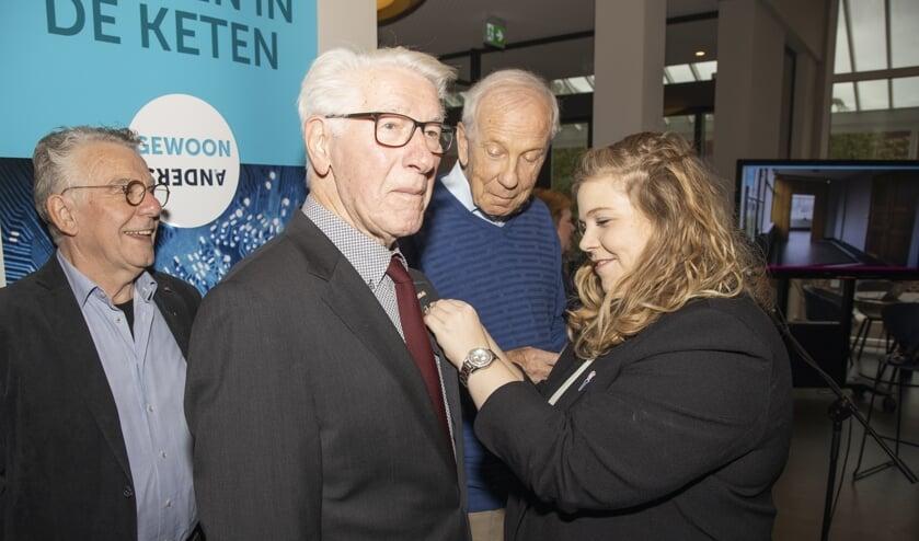 Wethouder Anne Thielen speldt de onderscheiding op bij Harrie Bloemen.