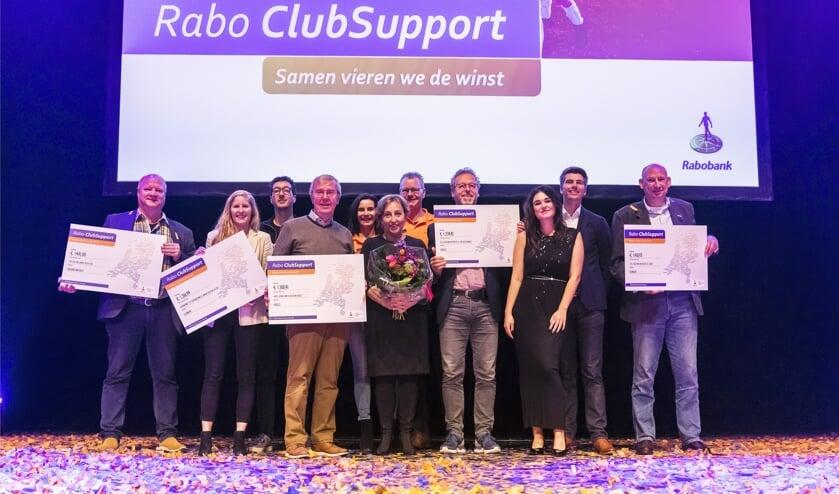 Vertegenwoordigers van de clubs met hun cheques, samen met Rabo-collega's Susanne Stevens, Twan Litjens, cabaretière Karin Bruers, zangeres Nienke Wijnhoven en directeur Edwin de Bruijn (tweede van rechts). Foto; Paul Poels.