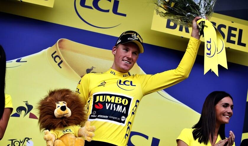 Mike Teunissen straalt op het podium van de Tour de France in de gele trui.