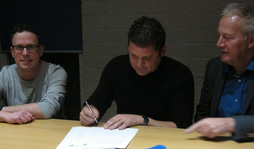 Patrick Wijnen (midden) zet zijn handtekening onder toeziend oog van Thijs Peeters (penningmeester, links) en Noud Creemers (voorzitter, rechts).