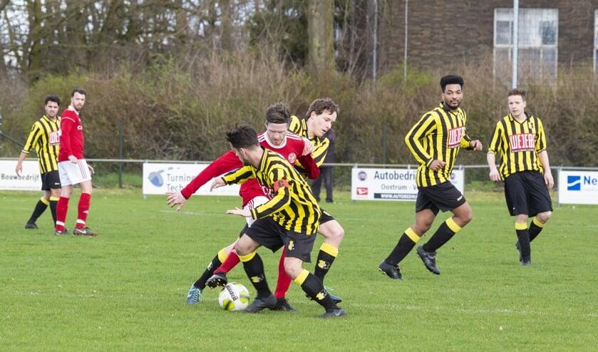 SV Oostrum-aanvaller Chris Wilschut (rood shirt) probeert twee spelers van BVV'27 af te schudden.