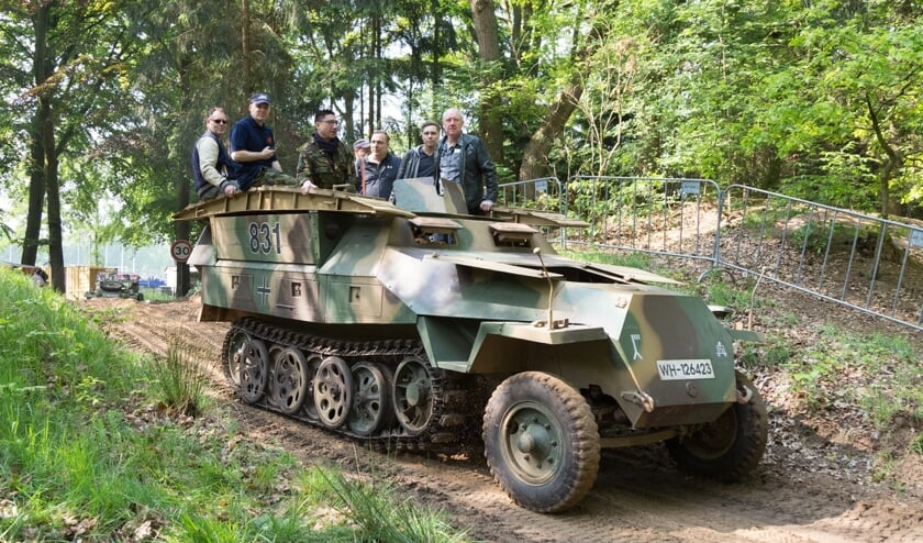 Een groepje bezoekers rijdt mee in een van de vele militaire voertuigen tijdens Militracks.
