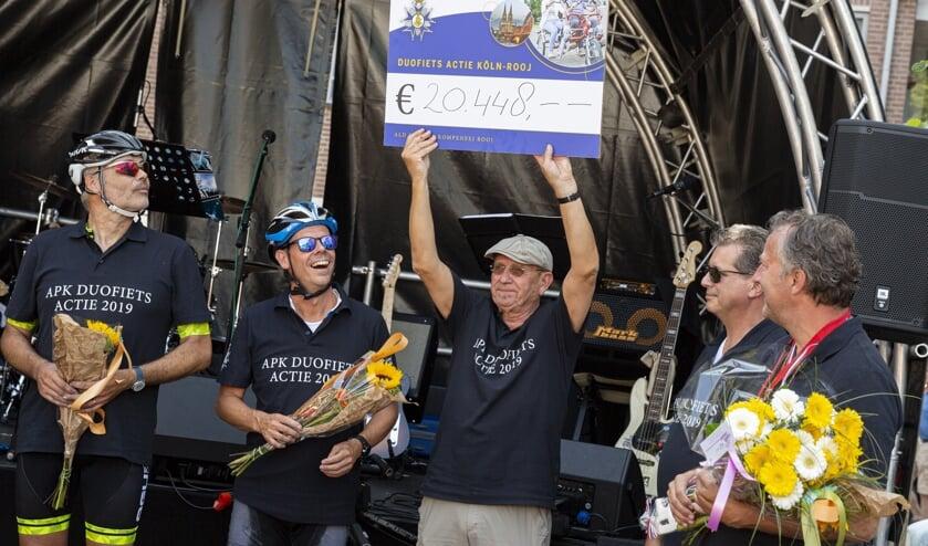 Hans Schambergen van de Ald Preense Kompeneej toont trots de cheque aan het publiek op het Schouwburgplein.