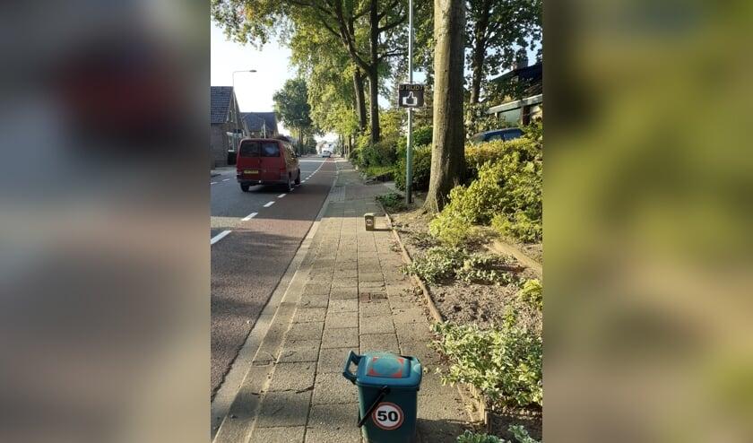 Groene afvalbakken met de 50 km-stickers langs de Meerlose Hoofdstraat.