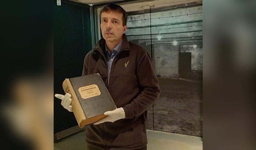 <p><strong>Museumdirecteur Erik van den Dungen&nbsp;</strong>met Het Dodenboek.&nbsp;</p>