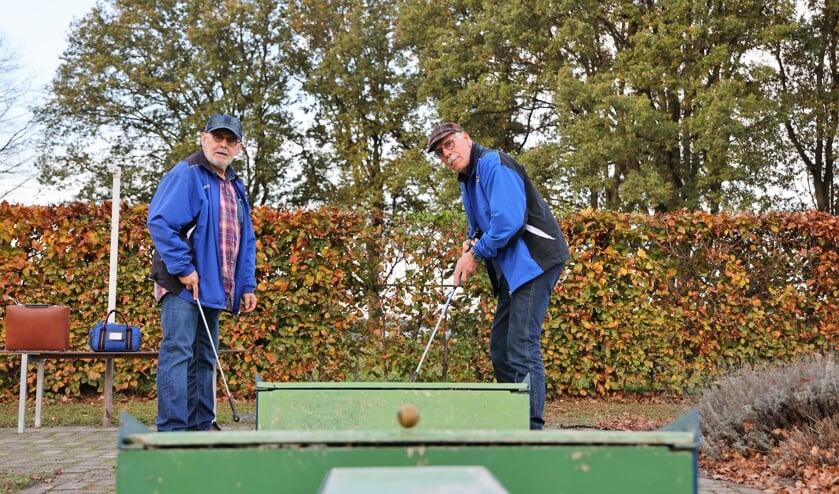 <p>Jan van der Hagen (rechts) en Jan Engels volgen de gespeelde midgetgolfbal naar de hole.</p>