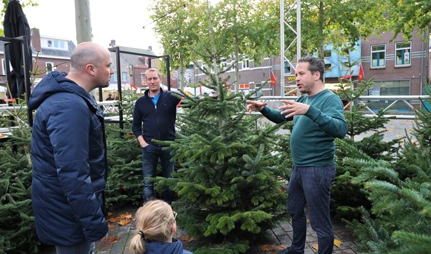<p>Gijs Schapendonk (rechts) en Giel van Driel (midden) verkopen kerstbomen.</p>