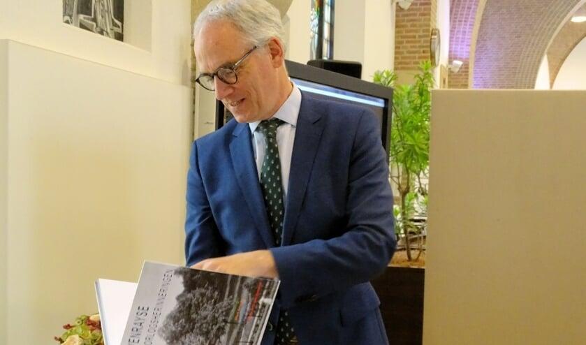 Burgemeester Luc Winants bladert door het boek Venrayse oorlogsherinneringen.