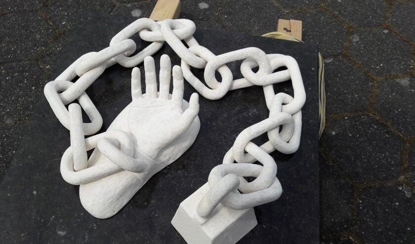 Het kunstwerk, gemaakt van grafsteen: Geketend.