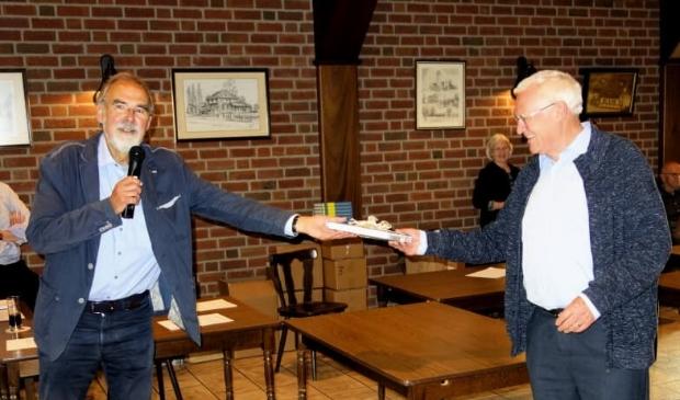 Hens Borkent (links) overhandigt het eerste boek aan Karel Janssen 'de Sikkeneur'