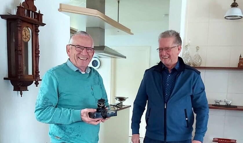 <p>Henk Janssen (rechts) overhandigt de externe schijf met het nieuwe digitale archief van Oostrum aan Joos Linskens.</p>