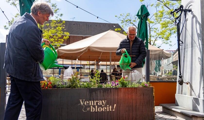 <p>Wethouder Jan Loonen (links) en initiatiefnemer Antoon Verlinden verrichten de symbolische openingshandeling bij de waterpomp op de Grote Markt in in Venray.</p>