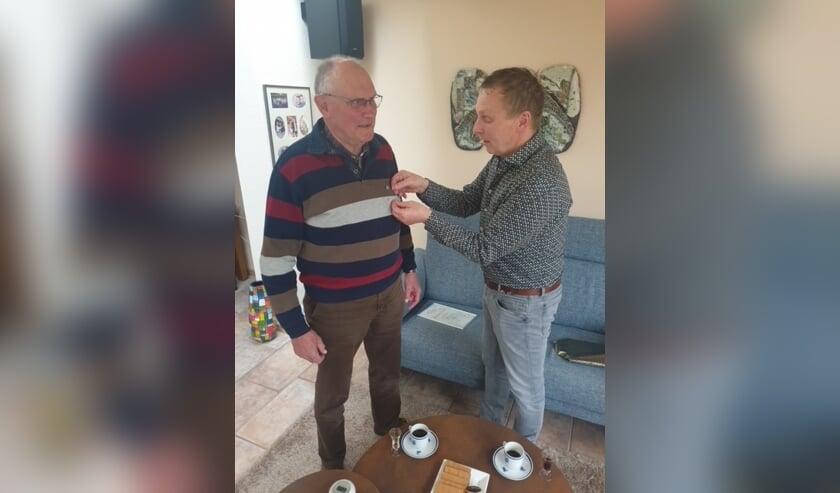 <p>Voorzitter Diederik Nijenhuis speldt Hans Gommans zijn jubileumspeld op. </p>