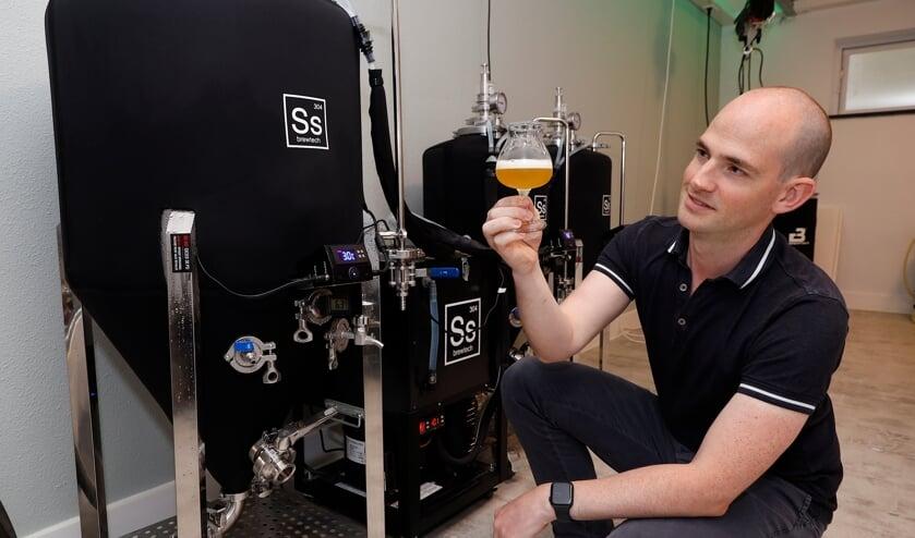 <p>Ben Theunissen kijkt in zijn nieuwe brouwerijtje goedkeurend naar zijn speciaalbiertje &#39;t Smakt.&nbsp;</p>
