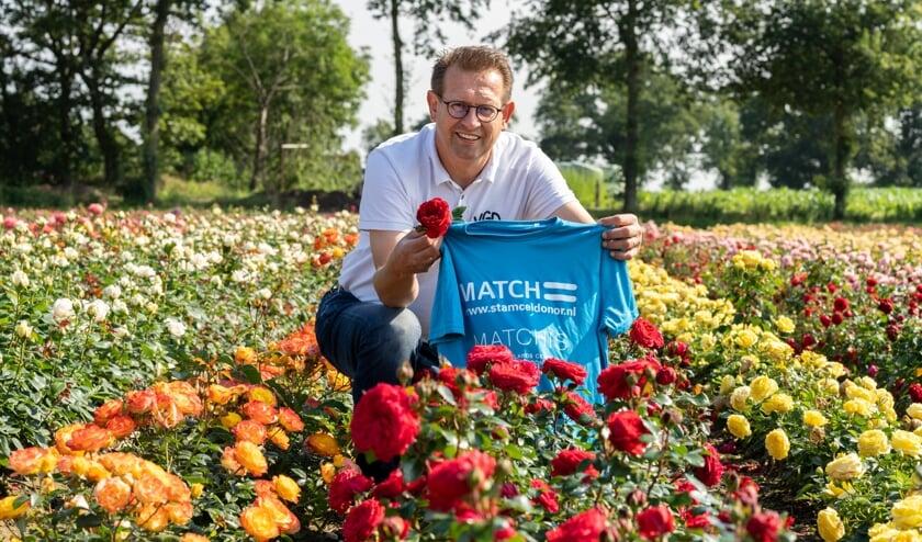 <p>Patrick Wijnhoven zitten trots bij zijn rozen en in het bijzonder de rode Rosa Matchis.</p>