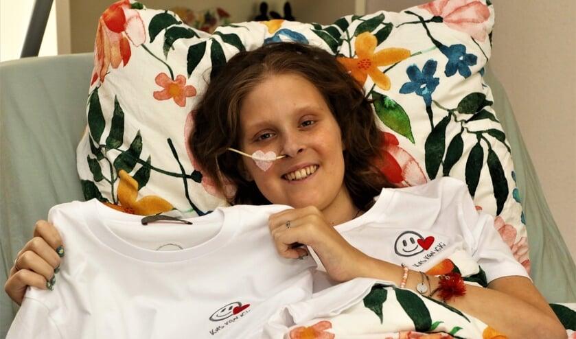 <p>Kiki toont trots het T-shirt waarvan de opbrengst naar het goede doel gaat.</p>