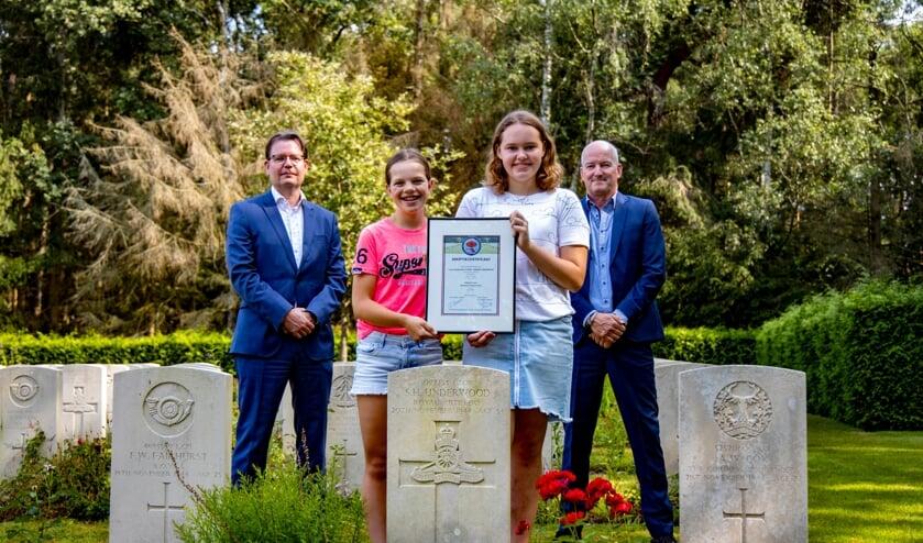 <p>Britt Jeucken en Maud Vogelzangs houden het adoptiecertificaat vast op de begraafplaats.</p>