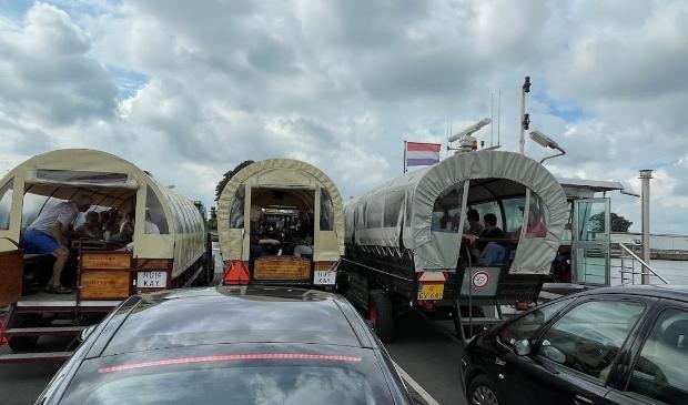 Met de huifkarren op de pont over de Maas