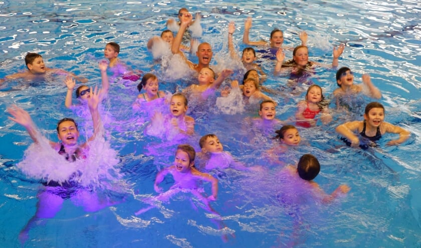 <p>Maarten van der Weijden zorgt woensdagmiddag in het zwembad in Venray tussen de kinderen voor het nodige waterplezier.</p>
