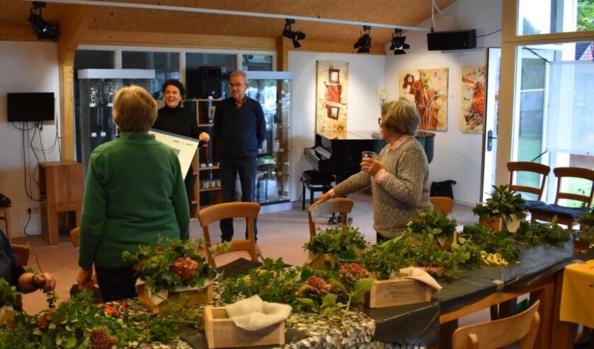 De gasten zijn druk bezig met hun herfststukjes, op de achtergrond staan Yonne Mous en Wim Fleuren.