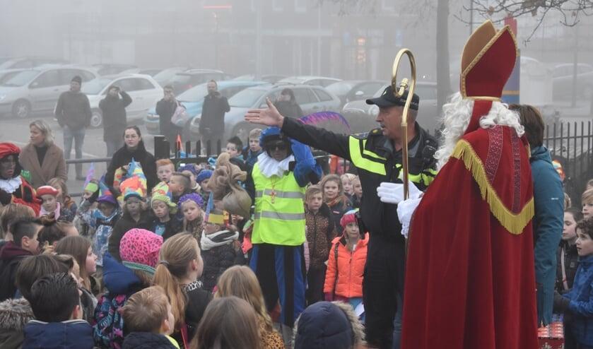 De politieagent vertelt dat de Sint zijn auto verkeerd heeft geparkeerd.