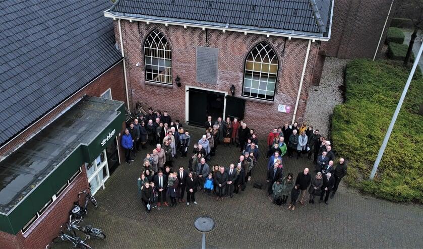 Leden van de hervormde kerk vormen het getal 200 op het kerkplein.