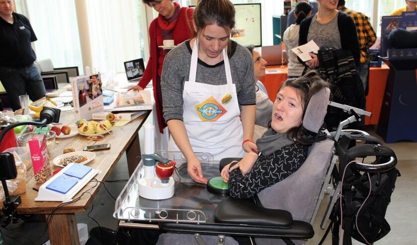 Yrsa zet met een druk op de knop de schilmachine aan het werk, die vervolgens haar appeltje schilt (Foto: Mirjam Terhoeve).