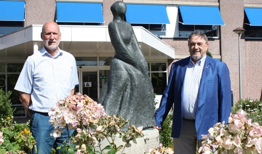 Henk Zwanenburg (links) en Jan Leenders bij het beeld van Paulina van Weel, recht voor de hoofdingang van het ziekenhuis in Dirksland (Foto: Kees van Rixoort).
