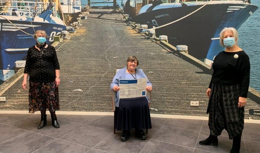 Twee vrijwilligsters en in het midden bewoonster Lies Westhoeve met de cheque.