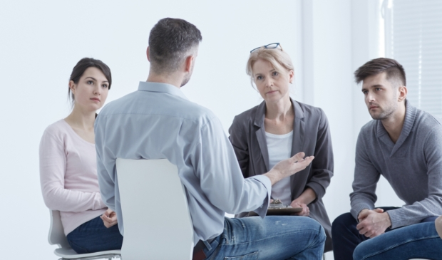 Distressed young man confiding to his supporting psychotherapy group