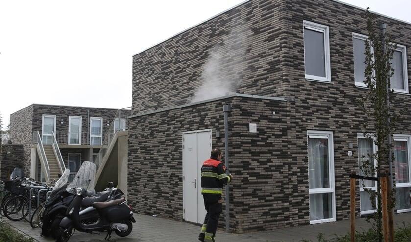 Rook is te zien, komend uit een bijgebouwtje.