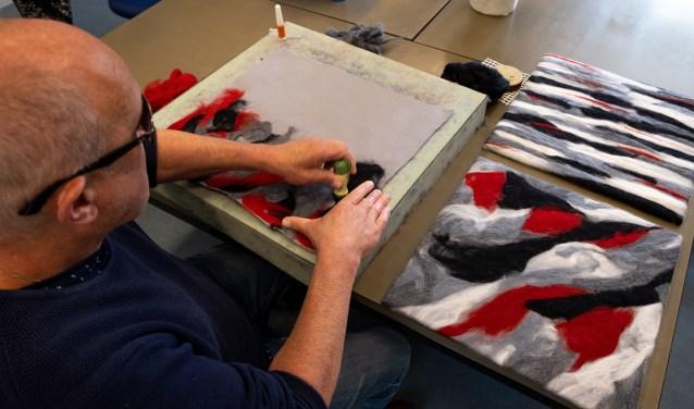 Slechtziende man maakt voelschilderij.