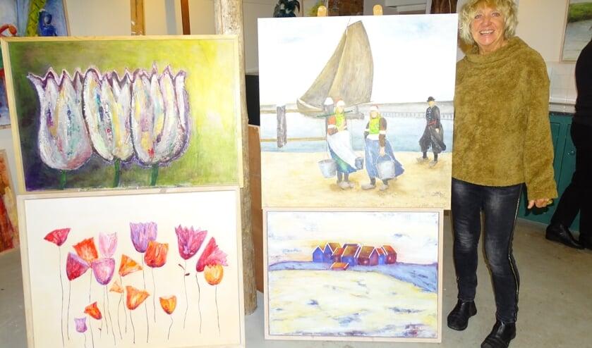 Trix Oosterman bij haar schilderijen.
