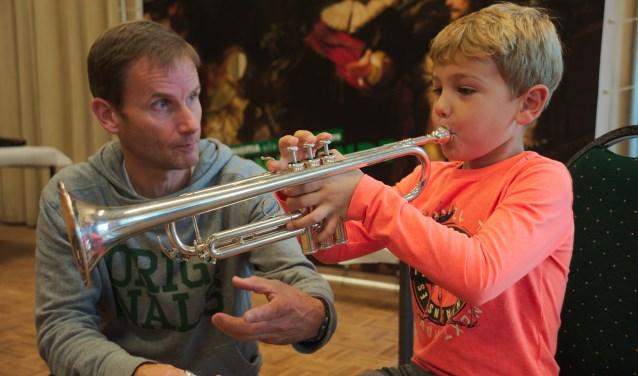 Joep (7) probeert de trompet uit bij trompetdocent Erik Torrenga.