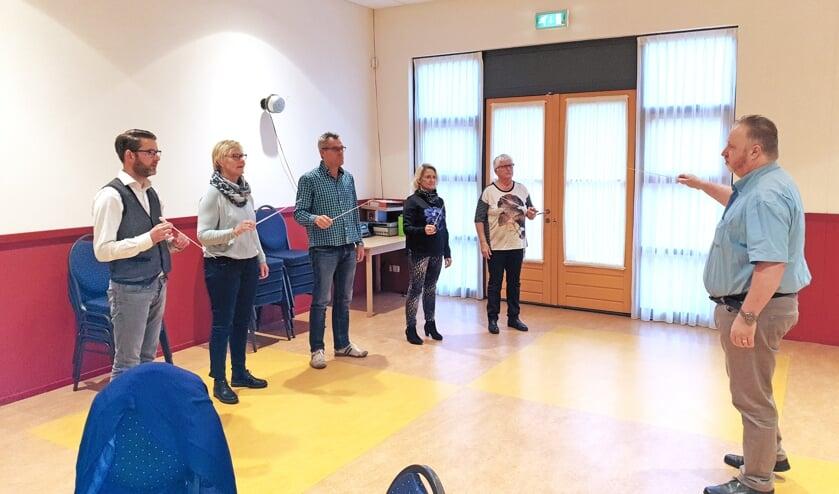De deelnemers krijgen de eerste beginselen van dirigeren bijgebracht door Karel Jongerling.