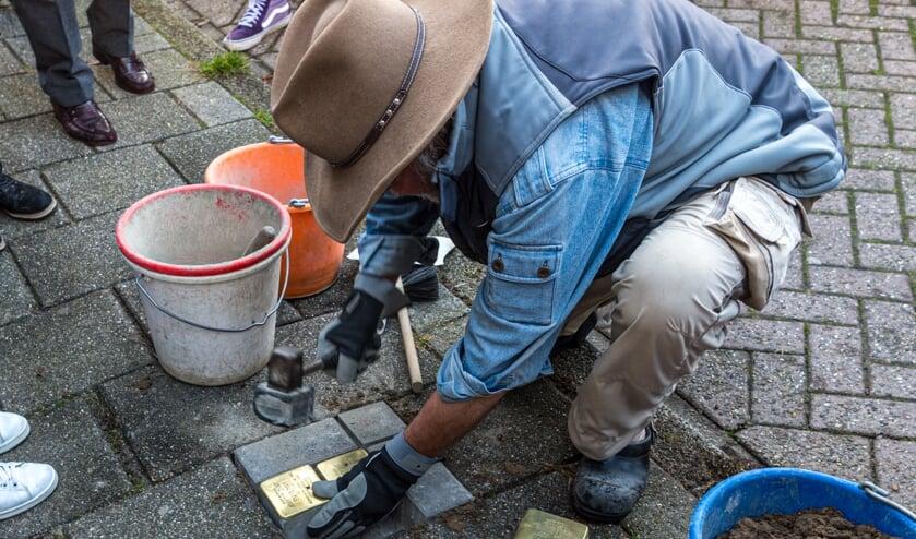Gunter Demnig legt de stenen in het wegdek.