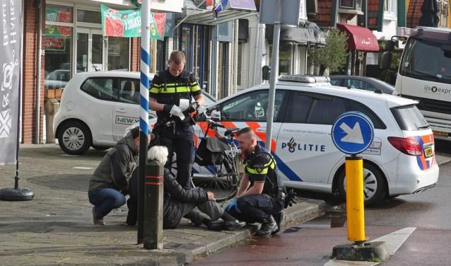 Agenten en een omstander verlenen de vrouw na de valpartij eerste hulp.
