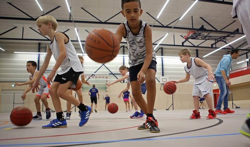 Basketballen gaat prima op de nieuwe sportvloer.