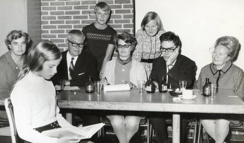 Brenda Terpstra die in oktober 1969 als elfjarige scholiere in hetkader van de Kinderboekenweek een voorleeswedstrijd won. Namen van de juryaan tafel zijn: V.l.n.r.: Mw. de Jong-den Baas, de Heer Kleinbloesem(bestuurslid bieb), Maud Stolk, Adrie Geus (administratie bieb). Helemaalrechts directeur Mw. Wilhelm-Glas.