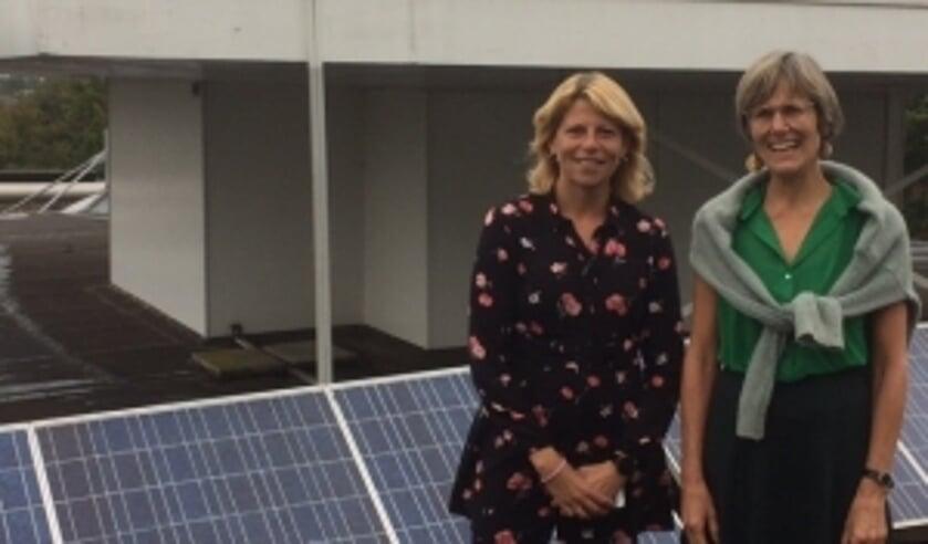 Zonnepanelen op het dak van het gemeentehuis. Mandy Elfferich en Jacobien van Beijen laten zien dat de gemeente zelf ook meedoet.