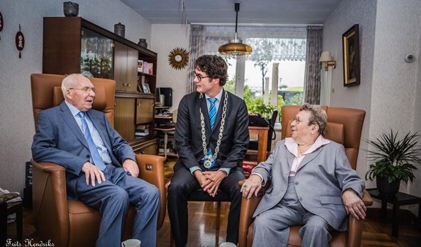 De heer en mevrouw Hendriks krijgen bezoek van loco-burgemeester Merijn Snoek.